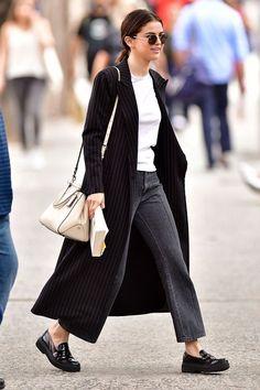Como ser casual e estilosa por Selena Gomez. Maxi casaco preto risca de giz, t-shirt branca, calça jeans preta desbotada, mocassim de vinil preto