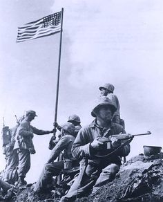 The First Flag Raising on Mount Suribachi, Iwo Jima, 23 February 1945. Marines of the 28th Regiment, Fifth Marine Division, hoist the U.S. flag on a piece of pipe, at about 1020 Hrs. after capturing the summit of Mount Suribachi. Holding the flagpole are Sergeant H.O. Hansen, Platoon Sergeant E.I. Thomas, and First Lieutenant H.G. Schrier. In the foreground Private First Class J.R. Michaels stands guard with an M-1 Carbine. Corporal C.W. Lindberg is behind him