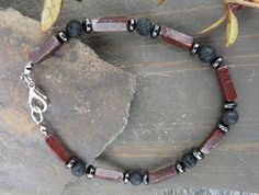 """Mens Gemstone Bracelet Brecciated Jasper by TheCrystalCavern on Etsy.com  Round lava rock beads with breciated jasper rectangle and hematite rondelle beads blend together in this striking mens bracelet. Strung on strong beading wire and finished with a silver plated lobster clasp.    Length 9"""" / 23cm."""