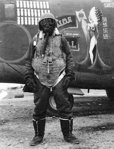 """An aircrewman with the 743rd Bomb Group standing in front of B-24H Liberator """"TePee Time Gal"""" wearing typical protective clothing, San Giovanni Airfield, Foggia, Italy, 1944-45."""