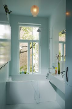 small space used well . shower head . window . pure design of bathtub and sink .