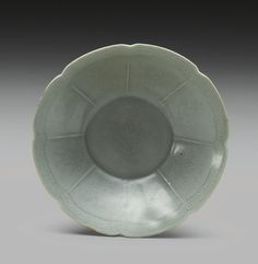 A KOREAN CELADON FOLIATE RIM DISH GORYEO DYNASTY, 12TH CENTURY with straight flaring sides rising to the notched rim, the interior divided into eight panels, each incised with a stylized lotus spray, beneath a foliate scroll at the rim, the well incised with a larger lotus spray, the incised sprays repeated on the exterior and base, all covered with a gray-green glaze, the base with three spur marks. Diameter 4 1/2  in., 11.5 cm