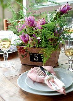 Até na hora de enumerar a mesa dá para acrescentar charme à cerimônia. O cachepô criado pela La Calle Florida tem um retângulo pintado com tinta de lousa para a marcação
