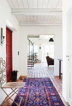 Modern farmhouse in Sweden - Red Door, bright Kilim on tile floor, wood plank & beam ceiling, white walls, curved metal staircase...