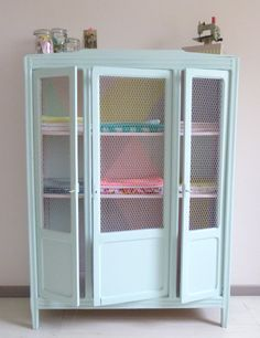 An plain white armoire with glass doors was given new life with aqua paint on the outside and pink, yellow and aqua geometric pattern on the inside. The glass was replaced with chicken wire. Love it!