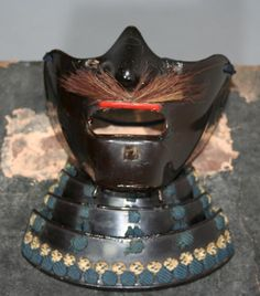 This mempo is a very early style black lacquer sugake laced mempo of the style often used by the Date clan.