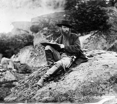 Timothy O'Sullivan's stereograph view of Civil War sketch artist Alfred Rudolph Waud. Waud is posed here in Devil's Den with his sketchbook. This view was taken circa July of 1863.'