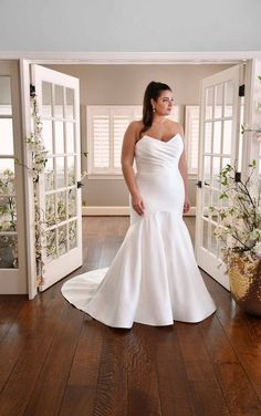 This wedding dress pulls inspiration from Old Hollywood for a design made for the modern bride. On the bodice, the fabric overlaps for a glamorous ruched effect while providing ultimate support and comfort. The pointed details on the classic sweetheart neckline adds a modern twist. This wedding gown hugs the body, with a comfort lining layer for all-day comfort. The skirt flares out to a voluminous full train, complete with fabric-covered buttons trailing to the hem of the skirt. Bridal Collection, Dress Collection, Designer Wedding Dresses, Wedding Gowns, Essense Of Australia Wedding Dresses, Simple Gowns, Mermaid Silhouette, Floral Lace Dress, Plus Size Wedding