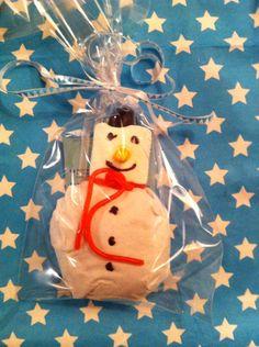 Sneeuwpop traktatie Lijf van krentenbol met wit servetje, hoofd van marshmallow, petje is een dropje, neus van dropstaafje, sjaal een aardbeien dropveter.