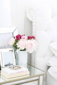White flower vase and pink blooms.