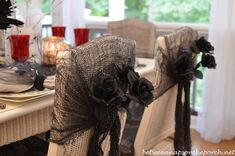 Chair Backs Decorated with Black Roses and Spiders for Halloween Table  this could be done for all kinds of holidays or weddings, just dye the fabric-cheesecloth whatever color