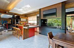 Decoração de casa de praia. Na sala de jantar, parede de tijolinhos, mesa de jantar retangular de madeira, cristaleira azul e pendente. Banquetas de madeira e luz natural na cozinha.