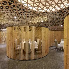 A woven net of bamboo creates a curved suspended ceiling inside this restaurant.