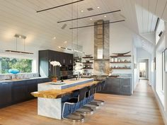 live-edge plank hugging around that center island with a double waterfall edge counter top  berg-design-montauk-monroe-drive-house-designboom-08