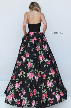 The Sherri Hill 50333 prom dress features a stylish ball gown silhouette in vibrant floral prints. The halter top is held with a slim strap, accentuating the semi-open back. The printed full skirt is enriched with a mesh lining, and flows out with a court train. The box-pleated top-skirt conceals a duo of side pockets.