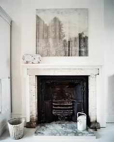 white and black fireplace and lacy art over the marble mantle