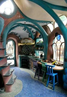 Lovely cob house interior. Just look at those colorful, swooping ceiling supports and that lovely, steep staircase!
