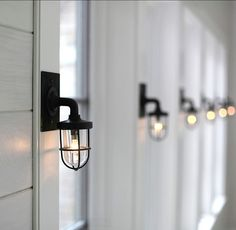 "The hallway that leads to the bedrooms carry beautiful nautical sconces from ""Marsten and Langinger"" (UK). - Classic Shingle Beach Cottage with Neutral Interiors"