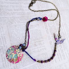 Rhapsody necklace. Embossed, patinated, brass bird and disc on silk and chain with Czech glass, lucite.