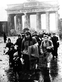 German women and children walk through the ruins of Berlin, 1945.
