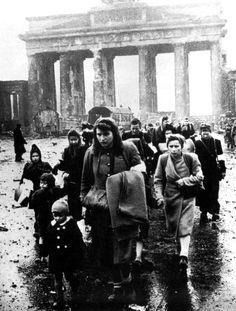 German women and children walk through the ruins of Berlin, 1945.