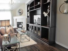 A large dark wooden entertainment center matches the dark hardwood floor and contrasts the neutral walls in this transitional living room. A contemporary glass coffee table sitting on a shag rug and matching end table add angle to the room. A contemporary mounted candle holder and a mirror above the fireplace decorate the room.
