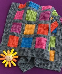 Intarsia blocks worked in six cheerful colors pop against a neutral gray background in a fun, modern design.