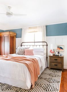 Beautiful master bedroom with traditional furniture, black and white area rug, and peach and blue accent colors.