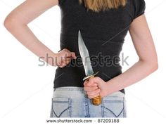 Young woman holding knife behind her. Isolated on white background - stock photo