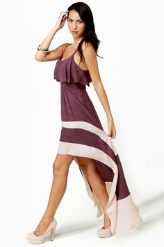 """Grace any riverbank or promenade with a rippling tail hem trailing behind in the Merrily Rolling Along High Low Purple Dress! Beige color-blocking works its way up a full skirt, while a fitted bodice boasts a top flounce that overlaps an open back keyhole. Adjustable shoulder straps. Elastic at back of waist. Dress is lined to mid-thigh. Belt not included. Model is wearing a size small. Small measures 31"""" long, plus adjustable straps; 22"""" longer at back. 25"""" waist (relaxed). 32..."""