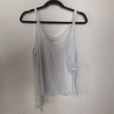 Silence + Noise urban outfitters tank top White tank top. One side is longer and the other side has a deep pocket for style. Bought at urban outfitters and is perfect with a Bralette underneath. The sides are low cut. There is a small blue dot in last photo, this is inside the rim and may be able to be blenched out. silence + noise Tops Tank Tops