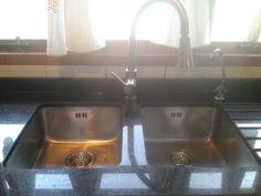 lavaplatos de acero inoxidable de 2 cuberas con separación de granito y cubierta ranurada para escurrir el agua.
