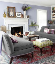 A white and marble fireplace pops against a lavender wall in the living room of this Kansas home.