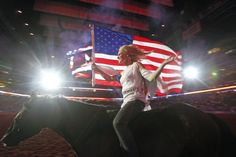 Niki Cammaert carries the American flag while riding a horse bareback during the National Anthem before at the Houston Livestock Show and Rodeo on March 5, 2012.  Photo by James Nielsen / Houston Chronicle
