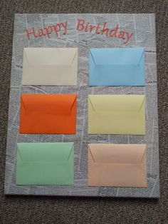 Leuk verjaardagskado. Een canvasdoek beplakt met oude kranten, vervolgens zelf enveloppen gemaakt van gekleurd papier en in iedere envelop een kado.