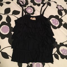 Ruffled top  EUC top, had this for a few years now! It's really cute and has adjustable straps. Could honestly be considered a crop top, but does go to the top of my jeans on me. Looks great with a cardigan and jeans, but could pretty much go with anything. Looking for a good home. Price is firm, but could be negotiable. lowball offers Hollister Tops Tank Tops