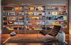 Nessa estante destaque para a iluminação e para a escada metálica que além de auxiliar no acesso á prateleira mais alta dá um charme à decoração.