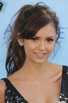 The light touch of bangs frames Nina Dobrev's face, making it look less oval and more heart-shaped.