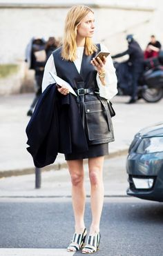 Pernille Teisbaek wears a white top, black belted vest, black skirt, and striped heels