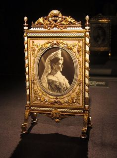 This fire screen picture frame designed by Carl Fabergé was crafted by workmaster Henrik Wigstrom in St. Petersburg around 1910. It is made of gold and features a picture of Tsar Nikolay II on one side and Alexandra Feodorovna on the other. It was probably a gift from the tsar to his mother ~