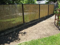 Paint pipes of chain link fence black and fit reed privacy fence in for an Asian look.