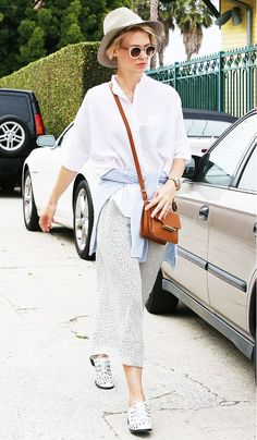 January Jones wears an oversized white button-down shirt, sweater tied around the waist, printed culottes, oxfords, a crossbody bag, round sunglasses, and a fedora