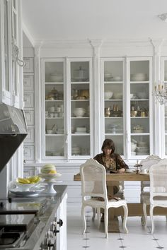 Beautiful full wall of white cabinets with glass doors for storage at Belgian photographer, Bieke Claessen's home.
