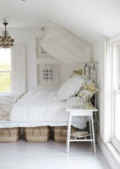 Love the chandelier, the iron bed frame, and the baskets underneath for pretty storage.