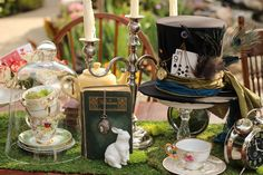 Alice in Wonderland | Mad Hatter Tea Party-themed vintage decor ideas. Moss runner, teacups, teapots, clocks, pocket watches, top hat, ceramic rabbit, glass cloche, candelabra, vintage book, skeleton keys, all combine to bring the magic and fantasy to life.