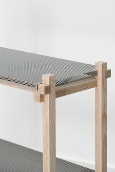 Hyllor i perforerad metall i en träkonstruktion.