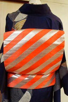 銀と朱色のバイカラーの斜めストライプがとびきりモダンで印象的な名古屋帯です。