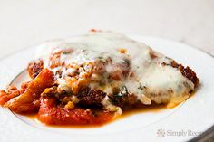 Classic Chicken Parm recipe with breaded chicken breasts, swimming in tomato sauce, topped with basil, and Mozzarella and Parmesan cheese. ~ SimplyRecipes.com