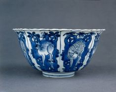 Porcelain bowl with high straight sdes and everted mouth rim, decorated in underglaze cobalt blue. Vertical panels on exterior with alternating spotted and white deer against rocks and plants. Similar panels on interior with plants and ornamental rocks, with a roundel of a deer in the centre. Ming Dynasty Wanli period. The British Museum.