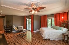 Transitional Master Bedroom with Ceiling fan, Hardwood floors, flush light, Pendant light, Crown molding, High ceiling. I like the room and the layout and the deck that you can walk out onto. Not a fan of the style of wood for the floor or the ceiling fan or the color of the curtains though.